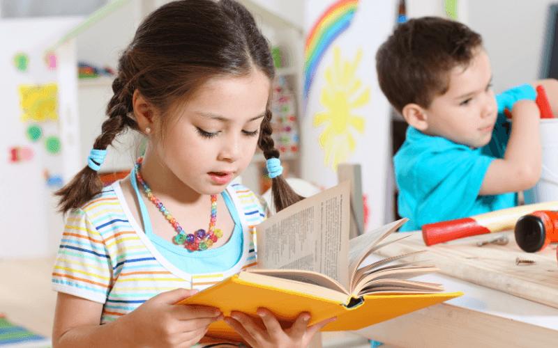 Dziewczynka czyta książkę w przedszkolu.